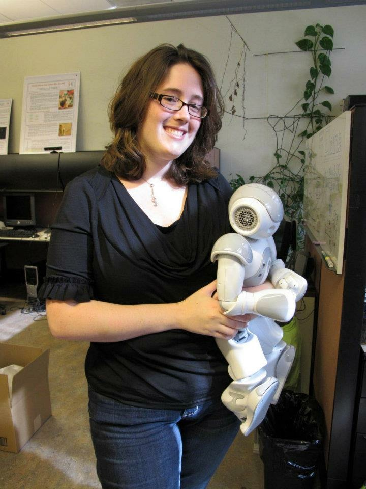 Photograph of Elaine holding a small grey and white robot.