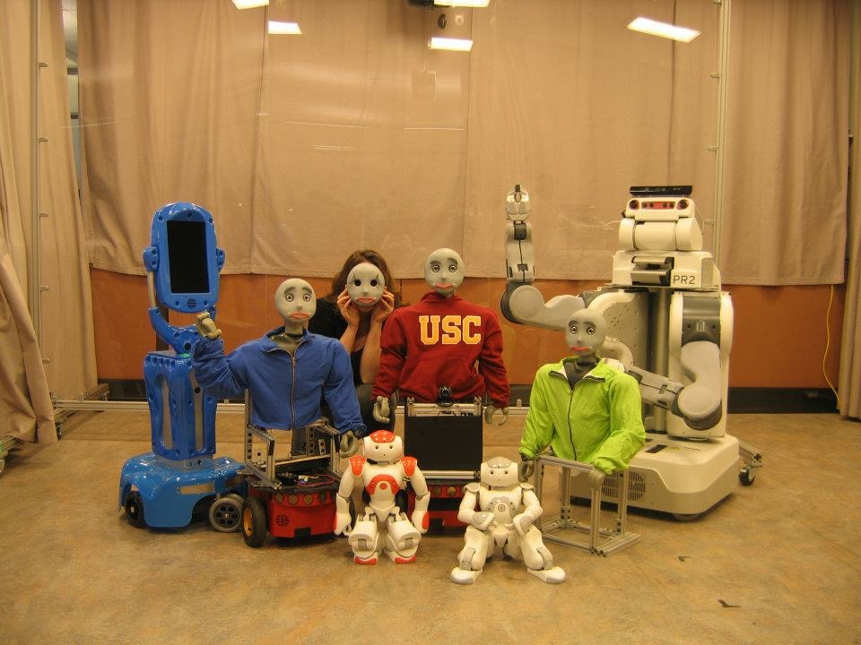 Photograph of Elaine pretending to be a robot in a group of robots