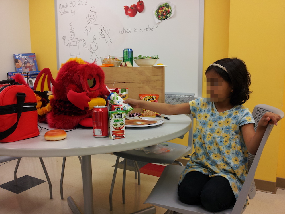 The small fuzzy robot Chili sits on a table among various food items, playing with a young girl of about five years of age.
